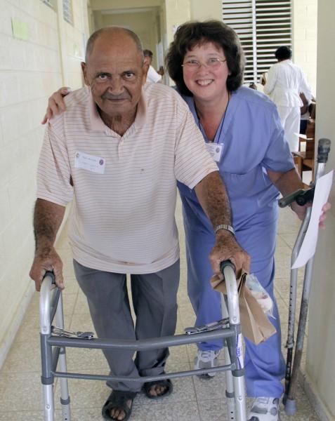 Anne Bena, un fisioterapeuta, ayuda a un paciente con un andador. Antes de recibir el andador con ruedas, el paciente, que Bena conoce desde hace cuatro años, utilizaba dos muletas para desplazarse. Foto: Lynette Wilson / Episcopal News Service