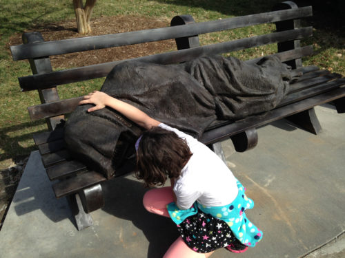 """The """"Homeless Jesus"""" sculpture is designed to be interactive and has drawn the attention of adults and children alike. Photo: Alleen Barber"""