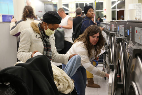 A volunteer helps a client load her washing machine at the Venice Beach Laundry Love on the last Monday in January.