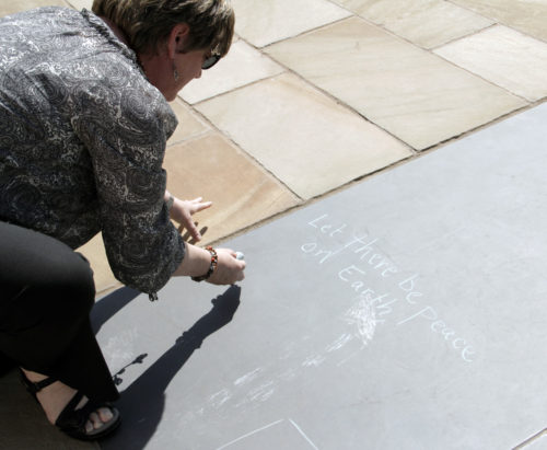 "Beth Crow, youth missioner in the Diocese of North Carolina, writes ""Let there be peace on earth and let it begin with me,"" on a blackboard panel during a visit to the Oklahoma City National Memorial & Museum. Photo: Lynette Wilson/ENS"
