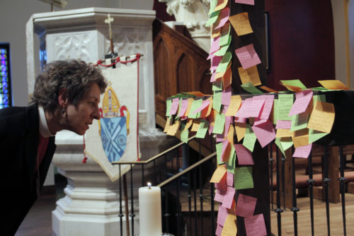 Presiding Bishop Katharine Jefferts Schori reads the intentions conference attendees placed on cross during the closing Eucharist of Reclaiming Gospel of Peace at St Paul's Cathedral in Oklahoma City. Photo: Lynette Wilson/ENS