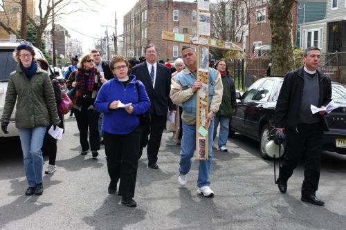Carlos Hernandez of Grace Van Vorst carries the cross, between the Rev. Laurie Jean Wurm (left), Rector of Grace Van Vost, and the Rev. Thomas Murphy, Rector of St. Paul's in Bergen. Photo: Nina Nicholson