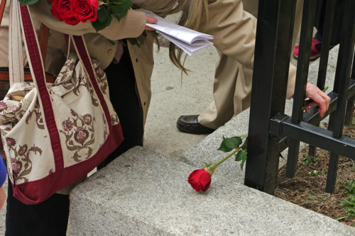 Jane Jackson of Grace Van Vorst places a rose at the first station. Photo: Nina Nicholson
