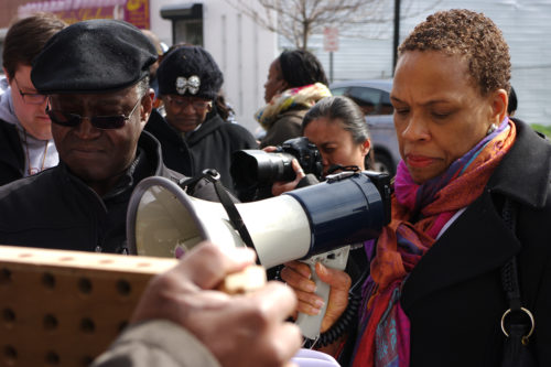 Sidney King and Carol Harrison-Arnold, Wardens of Church of the Incarnation, read at one of the stations while behind them Jersey Journal photographer Reena Rose Sibayan takes photos. Photo: Nina Nicholson