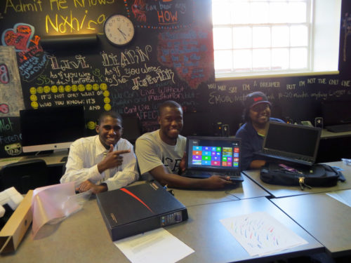 From left, Aquill Palmer, Tyron Morrison and Brittany Palmer show off computers provided to the Youth Center at Episcopal Community Services in Philadelphia thanks to St. Thomas Episcopal Church in the Diocese of Pennsylvania. Participants in the center's program, which helps teens and young adults complete their education and find jobs, decorate the blackboard behind them with sayings and drawings. Photo: ECS