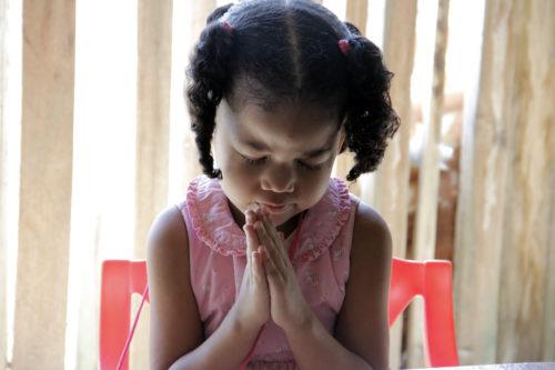 A young girl prays during Sunday school at the Episcopal Church in Brick Bay in Roatán, Honduras. Photo: Lynette Wilson/ENS