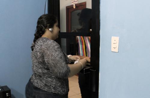 Una mujer que trabaja en la farmacia de Siempre Unidos en San Pedro Sula distribuye los fármacos a una mujer transexual. Foto: Lynette Wilson/ENS