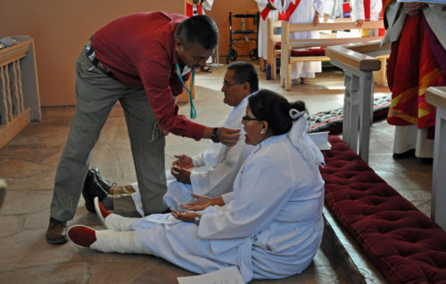 Kimball Shorty anoints Cathlena Plummer's mouth with corn pollen in a traditional Navajo blessing during the June 14 ordination of Plummer and Leon Sampson to the transitional diaconate at Good Shepherd Mission church in Fort Defiance, Arizona. Photo: Mary Frances Schjonberg/Episcopal News Service