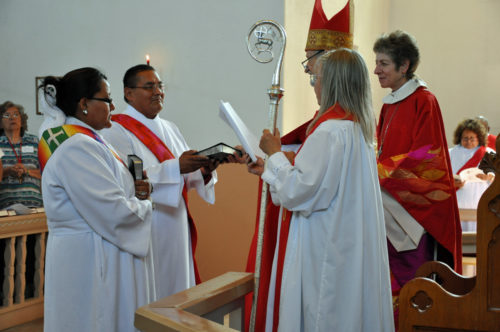 Navajoland Bishop David Bailey on June 14 hands newly ordained transitional deacon Leon Sampson a bible. Cathlena Arnette Plummer, another transitional diaconate who was ordained with Sampson at Good Shepherd Mission church in Fort Defiance, Arizona, stands to his right. The Rev. Chan Anaya, Good Shepherd's priest and a regional ministry developer, serves as Bailey's chaplain. Photo: Mary Frances Schjonberg/Episcopal News Service