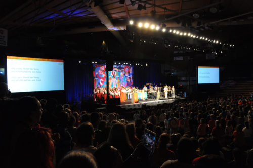 The Pavilion at Villanova University rocks when Episcopal Youth Event 2014 worships. The backdrop for worship is a quilt created by 13 Nigerian women who are HIV-positive. The Evangelical Lutheran Church in America loaned the quilt to EYE14. Photo: Mary Frances Schjonberg/Episcopal News Service