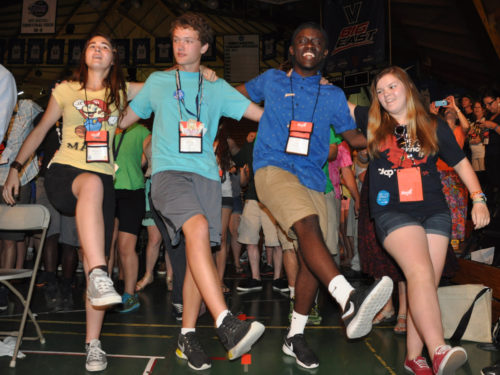 Three Episcopal Youth Event 2014 participants kick along to the prelude for EYE14's closing Eucharist July 12 inside the Pavilion at Villanova University. Photo: Mary Frances Schjonberg/Episcopal News Service