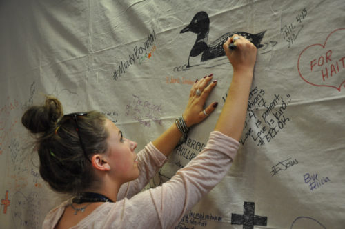 Sammy Fusco of Stillwater, Minnesota, finishes the detail work on a Common Loon, the state bird of Minnesota, that Johannah Frisby of St. Paul drew on one of the nine panels that form a prayer wall that greets Episcopal Youth Event 2014 participants when they enter the Pavilion at Villanova University for worship and plenary sessions. Photo: Mary Frances Schjonberg/Episcopal News Service
