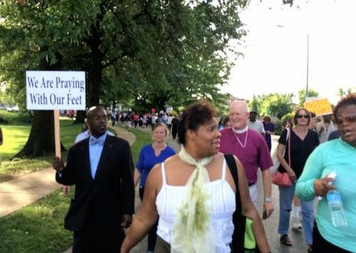 Wayne Smith, obispo [episcopal] de Misurí desfila el 14 de agosto, junto con clérigos y otras personas, a través del complejo de apartamentos de Canfield Green, donde el joven Michael Brown, de 18 años, fue muerto a tiros el 9 de agosto. Foto de Mike Angell.