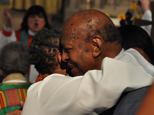 La Rda. Renee McKenzie, vicaria y capellana de la iglesia del Intercesor, saluda, durante el rito de la paz, al Rdo. Charles V. Willie, que predicó en las ordenaciones de las 11 de Filadelfia. Willie era vicepresidente de la Cámara de Diputados y miembro del Consejo Ejecutivo de la Iglesia Episcopal en el momento de las ordenaciones, pero renunció a ambos cargos como protesta cuando, tres semanas después, la Cámara de Obispos invalidó las ordenaciones. Willie leyó una de las lecturas durante la eucaristía del 26 de julio. Foto de Mary Frances Schjonberg para ENS.
