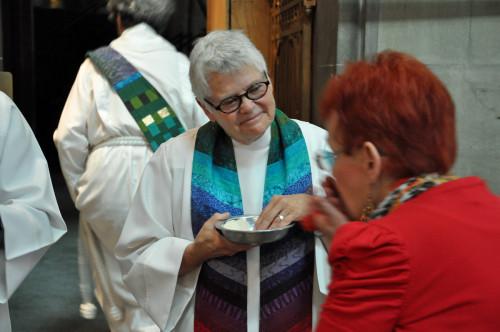 La Rda. Merrill Bittner, una de las 11 de Filadelfia que fueron homenajeadas en la celebración del 40º. Aniversario el 26 de julio, da la comunión en el oficio eucarístico. Foto de Mary Frances Schjonberg para ENS.