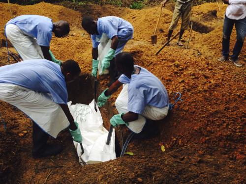 Unos voluntarios sepultan un cadáver —preparado conforme a normas de enterramiento seguras para garantizar que no presente riesgos de salud para otros y que interrumpa la cadena de transmisiones de una persona a otra— en una tumba de Kailahún, Sierra Leona. Foto de Tarik Jasarevic/Reuters/OMS.
