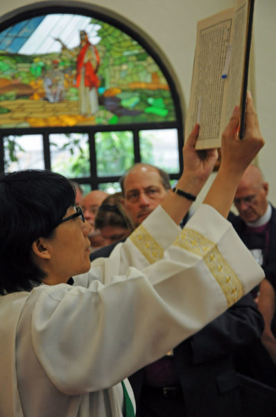 The Rev. Ching-yi Tsai, deacon at the Episcopal Church of St. John's Cathedral in Taipei, elevates the gospel book Sept. 21 during Eucharist attended by members of the House of Bishops. Photo: Mary Frances Schjonberg/Episcopal News Service
