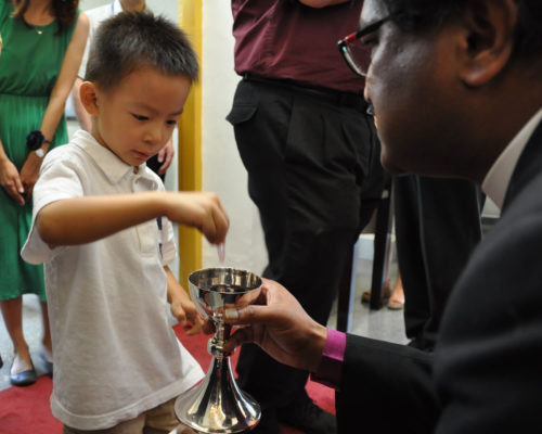 Diocese of Rochester Bishop Prince Singh holds the chalice as a boy intincts Sept. 21 during Eucharist at the Episcopal Church of St. John's Cathedral in Taipei. Photo:Mary Frances Schjonberg/Episcopal News Service