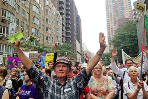 Don Robinson, a member of St. John's Episcopal Church in Northampton, Massachusetts, and a trustee of the Diocese of Western Massachusetts, lifts his hands during a moment of silence at the People's Climate March Sept. 21, in New York, two days before the United Nations' Climate Summit commenced. Photo: Amy Sowder