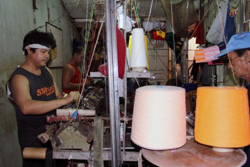 Los hombres tejen sombreros, bufandas y suéteres en talleres como estos en la aldea Igorot. Foto de Lynette Wilson para ENS.