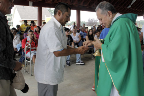 It touches Father Tony to administer the Eucharist to men with calloused hands, because in Latino culture, women are more likely to present themselves for the Eucharist.  Photo: Lynette Wilson/ENS