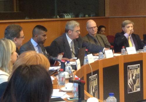 El Rdo. Mark Barwick (segundo de derecha a izquierda) presenta ante el Parlamento Europeo los resultados de un informa sobre violaciones de los derechos humanos en Irán. Foto por cortesía de DHSF.