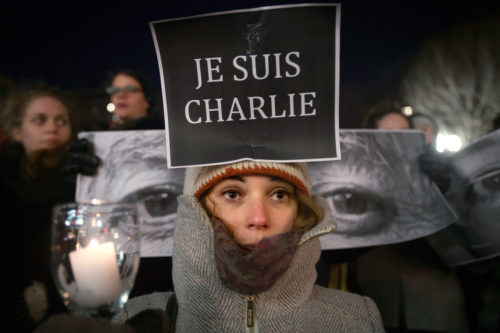 Amandine Marbach from Strasbourg, France, takes part in a vigil to pay tribute to the victims of a shooting, by gunmen at the offices of weekly satirical magazine Charlie Hebdo in Paris. Photo: Reuters/Carlo Allegri