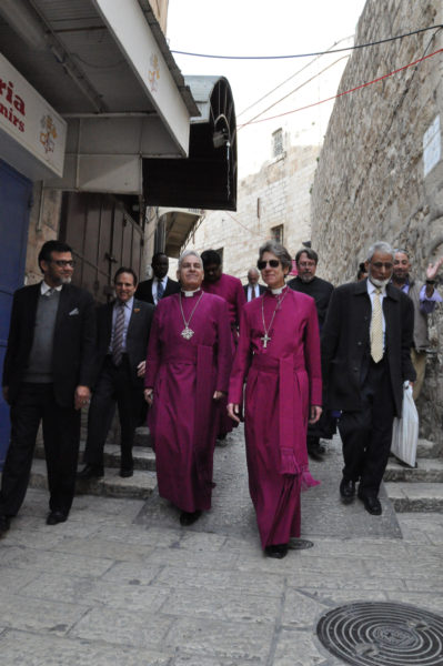 Wearing cassocks, Anglican Bishop in Jerusalem Suheil Dawani and Episcopal Church Presiding Bishop Katharine Jefferts Schori lead the interfaith delegation through the streets of Jerusalem's Old City. Walking behind, from left, are •Azhar Azeez, president of the Islamic Society of North America [ISNA); Rabbi Steve Gutow, president of the Jewish Council for Public Affairs (JCPA); •Mohamed Elsanousi, director of external relations for Finn Church Aid; •Bishop Prince Singh of the Episcopal Diocese of Rochester; •Rabbi Leonard Gordon, interreligious relations chair for JCPA; •The Rev. Charles K. Robertson, canon to the presiding bishop; and Sayyid Syeed, national director of interfaith and community alliances for ISNA. Photo: Matthew Davies/ENS