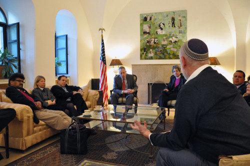 El grupo interreligioso se reúne con el cónsul general de EE.UU. Michael Ratney (sentado a la derecha de la bandera de EE.UU.). Foto de Matthew Davies/ENS