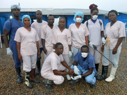 Many Cuttington University students, faculty and staff are employed at the International Medical Corps' Bong County Ebola Treatment Unit in Suakoko District, awaiting the university to reopen. They include Juyah J. Massaqui, sprayer; Chris N. Kollie, sprayer; Alex D. Iolleh, safety monitor; Jerome D. Padmore, sprayer, nursing student Sophie Jarpa, wash supervisor, Cuttington graduate Nurse Nameyeah D. Dunn; nursing student Eileen M. Gbassagee, dispenser, nursing student Love Fassama, nurse aid. Photo: Cuttington University