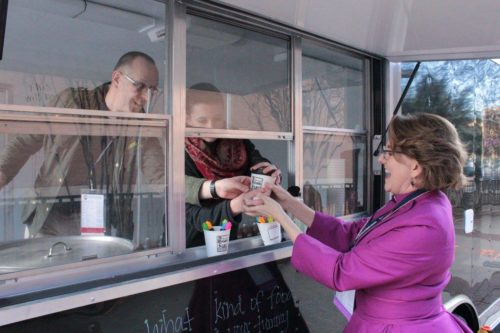 The Rev. Nils Chittenden, who at that time was the diocesan minister for youth and the Episcopal chaplain at Duke University, and A Moveable Feast Coordinator Caitlyn Darnell serve hot cider to North Carolina Bishop Suffragan Anne Hodges-Copple during diocesan convention in late November where the mobile campus ministry made its debut. Photo: Diocese of North Carolina via Facebook