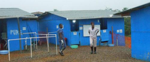 """El estudiante Chris N. Kollie, que trabaja rociando desinfectante, y la estudiante de enfermería Sophie Jarpa, que es supervisora de lavado, se encuentran en servicio activo en la Unidad de Tratamiento del Ébola en el Condado de Bong, en tanto el condado disfruta del estatus de """"ningún caso nuevo"""" por espacio de más de un mes, gracias en parte a los voluntarios y a la administración de la Universidad de Cuttington. Foto/Universidad de Cuttington."""