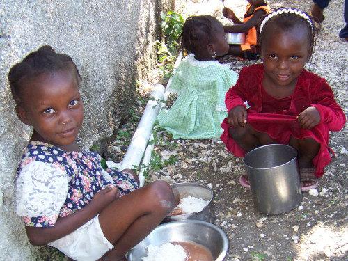Alumnas de la escuela de San Pablo, en Petti Trou de Nippes, Haití, en el momento del almuerzo. La escuela, fundada hace 25 años por el Proyecto Haití de Colorado, ofrece comidas nutritivas a más de 700 estudiantes todos los días. Foto del Proyecto Haití de Colorado.