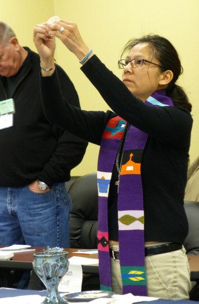 La Rda. canóniga Cornelia Eaton, miembro del PB&F y proveniente de Navajolandia, eleva la hostia en el momento de la fracción del pan durante la eucaristía del 25 de febrero. Eaton, que es canóniga del Ordinario en Navajolandia, fue ordenada sacerdote el 7 de febrero. Foto de Mary Frances Schjonberg/ENS.
