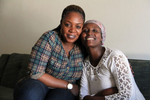 Congolese refugees Jeanine Balezi, an intensive-case manager for Refugee Focus, left, and Namughisha Nashimwe, pose for a photo in Nashimwe's apartment. Photo: Lynette Wilson/ENS