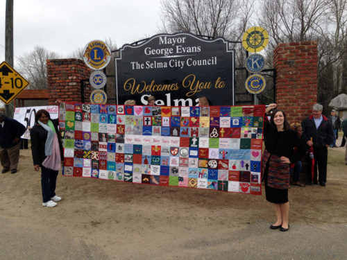 Deborah Brown, quilt volunteer, and Jamie Alvey, quilt designer and maker, display unity quilt on Montgomery side of bridge as walkers prepare to come home in faith. Photo: Kate Wood
