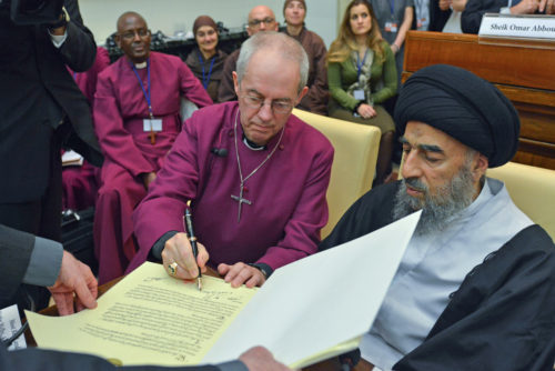Archbishop of Canterbury Justin Welby signs the Joint Declaration of Religious Leaders Against Modern Slavery on World Day for the Abolition of Slavery during a Dec. 2 meeting at the Vatican. The Grand Ayatollah Mohammad Taqi Al Modarresi of Iraq, another of the 12 religious leaders who signed the declaration, looks on. Photo: Global Freedom Network