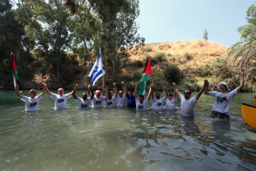"""EcoPeace Middle East gathers Israelis, Jordanians and Palestinians in the lower Jordan River for the """"Big Jump,"""" an event to raise awareness of river restoration efforts. Photo: EcoPeace Middle East"""