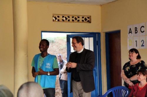 El Rdo. Frank Logue, canónigo del Ordinario en la Diócesis de Georgia, les habla a los refugiados durante una reunión comunitaria en el campamento de refugiados de Gihembe. Foto de Lynette Wilson/ENS.