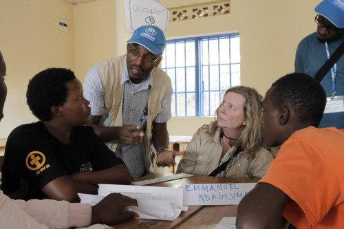 Paul Kenya, funcionario de reasentamiento que trabaja en Ruanda para el Alto Comisionado de las Naciones Unidas para los Refugiados, y Jessica Benson de la Diócesis de Idaho, hablan con estudiantes en una clase de Ingles como Segundo Idioma en el campamento de Gihembe. Foto de Lynette Wilson/ENS.