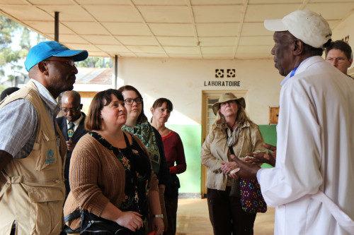 Paul Kenya, funcionario para el reasentamiento de la UNHCR en Ruanda; Deborah Stein, directora del Ministerio Episcopal de Migración y peregrinos de #ShareTheJourney escuchan al Dr. Pascal Kalinda Murego hablar acerca de la salud de los refugiados y de los servicios de salud que se ofrecen en el campamento de Gihembe. Foto de Lynette Wilson/ENS.