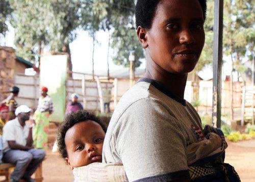 Una madre y un niño posan para una foto en el campamento de Gihembe. La mayoría de las familias del campamento están encabezadas por una mujer soltera. Foto de Lynette Wilson/ENS.