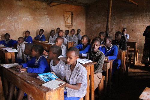 Alumnos de una escuela primaria estudian en un aula del campamento de Gihembe. Más de la mitad de los 14.500 residentes del campo son menores de 18 años. Foto de Wendy Johnson/EMM.