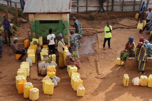 Residentes del campamento de Gihembe se congregan en torno a la llave de agua para llenar sus bidones. La escasez de agua es usual en el campamento. Foto de Wendy Johnson/EMM.