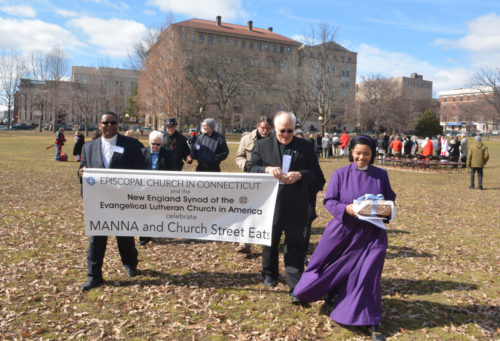 Carrying their banner in front, one of the four groups of clergy leave Bushnell Park in Hartford, Connecticut, after a communion service to visit the Manna Community Meals site. On the right is the Rev. Miguelina Howell, the vicar of Christ Church Cathedral, carrying a gift of bread for people at the site. Photo: Diocese of Connecticut