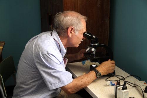 Episcopal missionary Martin McCann analyzes a specimen at his pathology laboratory in Dodoma, Tanzania. Photo: David Copley