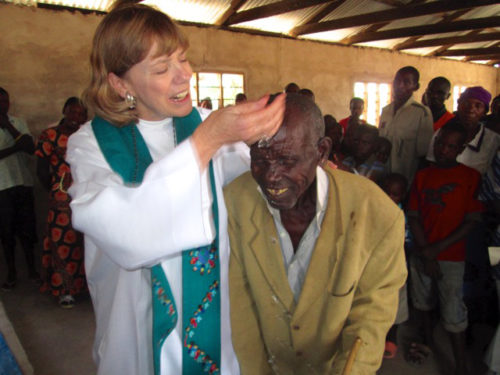 The Rev. Sandra McCann baptizes an elderly member of St. Peter's Anglican Church in Chikola, Tanzania, during one of her parish visits in the Diocese of Central Tanganyika.