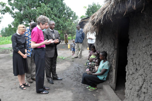During a July 2011 visit to the Democratic Republic of Congo, Presiding Bishop Katharine Jefferts Schori, the Rev. Margaret Rose and the Rev. Petero Sabune stop to say a prayer with widows in a community near the Anglican University of Congo in Bunia. Widows are considered outcasts in many Congolese communities. Photo: Matthew Davies
