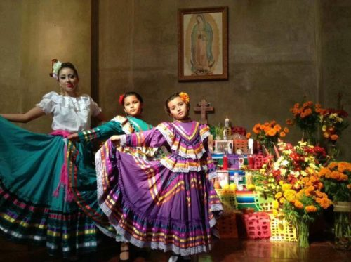Alondra Hernandez, Hannah Sands, and Camila Sands perform a ballet folklorico for the congregation at St. Paul's Cathedral in San Diego on Dia de los Muertos. The Latino cathedral community built and decorated the altar. The Hispanic and Anglo members of the cathedral have grown closer by way of the Latino Leadership Project, an initiative that received a Mission Enterprise Zone grant. Photo: Catedral San Pablo
