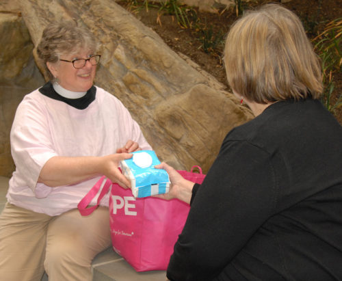 The Rev. Meredyth Wessman Ward, left, distributes feminine hygiene supplies as part of her urban ministry in Worcester, Massachusetts. Photo/Jane Griesbach